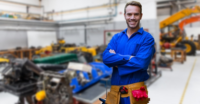 Mechanic standing with arms crossed in factory